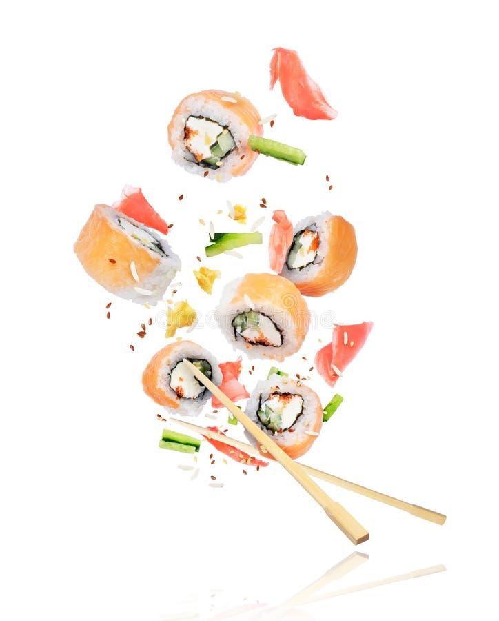 Stycken av den nya sushi med pinnar som frysas i luften på vit royaltyfri fotografi