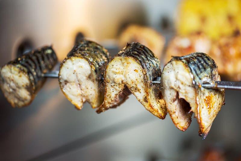 Stycken av den stekte fisken på en steknål royaltyfri fotografi