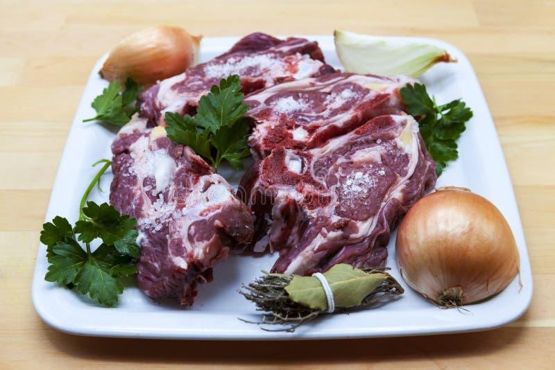 Stycken av det nya lammet på plattan Läckert fett-tailed lamm med löken på plattan Kött som ska grillas arkivbild