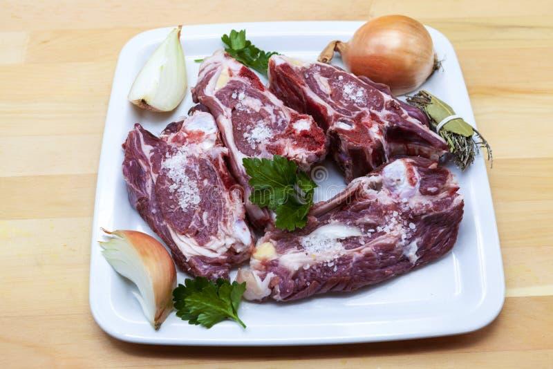 Stycken av det nya lammet på plattan Läckert fett-tailed lamm med löken på plattan Kött som ska grillas royaltyfria bilder