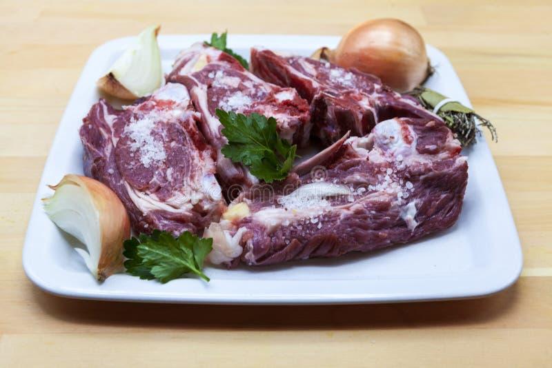 Stycken av det nya lammet på plattan Läckert fett-tailed lamm med löken på plattan Kött som ska grillas royaltyfri bild
