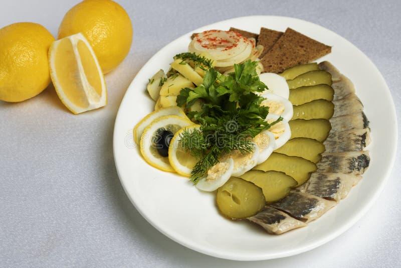 Stycken av fisken, ägg, bröd, gurkor, citron nära kalla mellanmål fotografering för bildbyråer