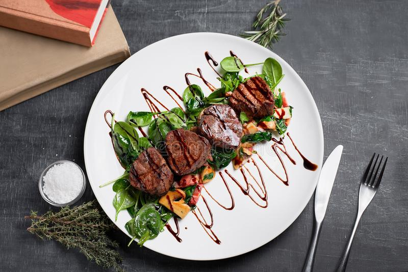 Stycken av grillat griskött på plattan med sallad arkivfoto