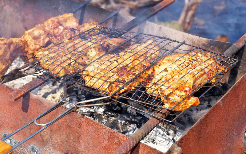 Stycken av grisköttkött på gallret fotografering för bildbyråer