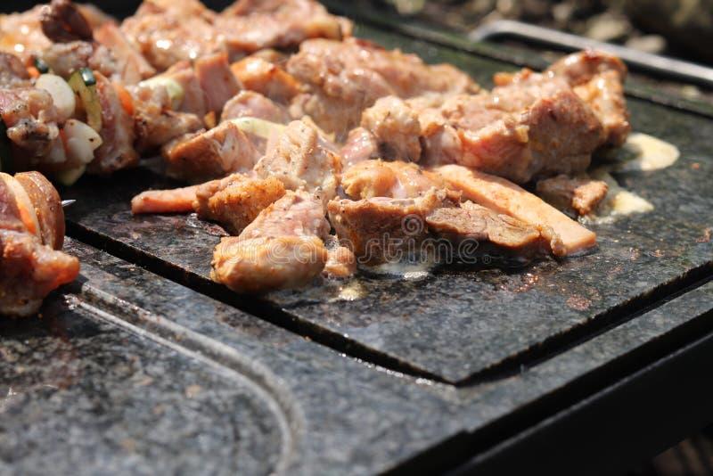 Stycken av höna- och kalkonkött som steker på den milda flamman för grillat idealt Rotat och oljt kött på det speciala skrivborde arkivbilder