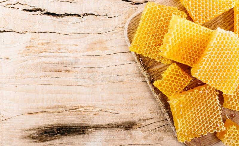 Stycken av honungskakan med honung fotografering för bildbyråer