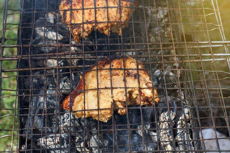 Stycken av kött lagas mat på ett grillfestgaller på träkol i rök royaltyfri foto