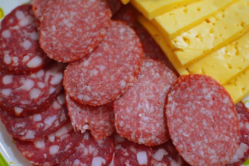 Stycken av korv och ost på en platta royaltyfria foton