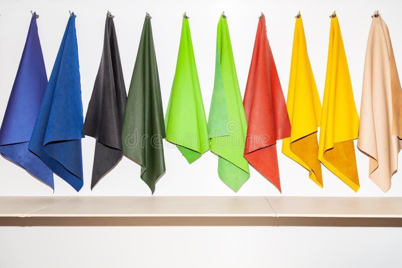 Stycken av lädermaterial till exempel i katalogen av olika färger för designstudion inställd på krokar i en textil royaltyfria bilder