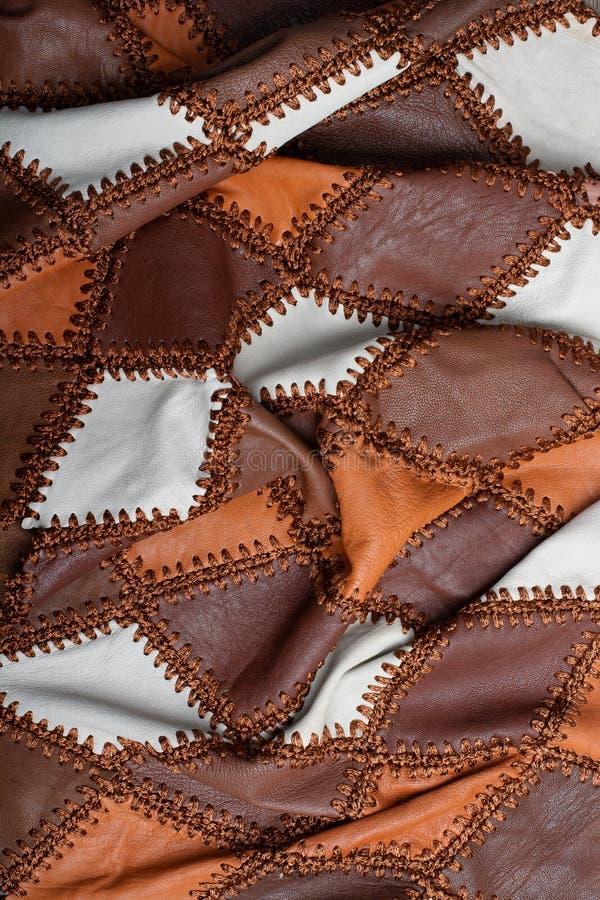Stycken av mång--färgat läder som sys med tråden, buckligt tyg arkivbild