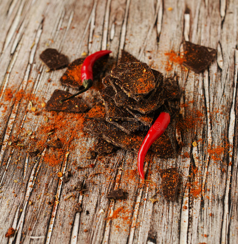 Stycken av mörk choklad med chili på svart kolbräde arkivfoto