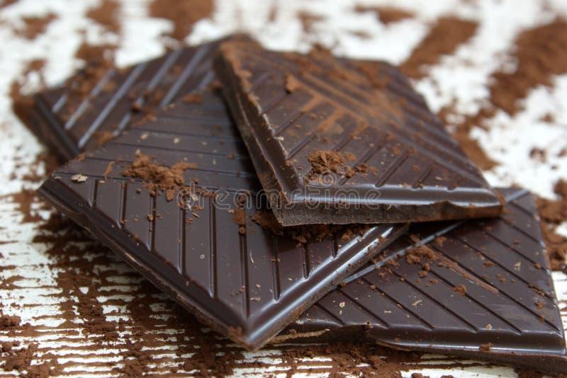 Stycken av mörk choklad med chokladpulver fotografering för bildbyråer