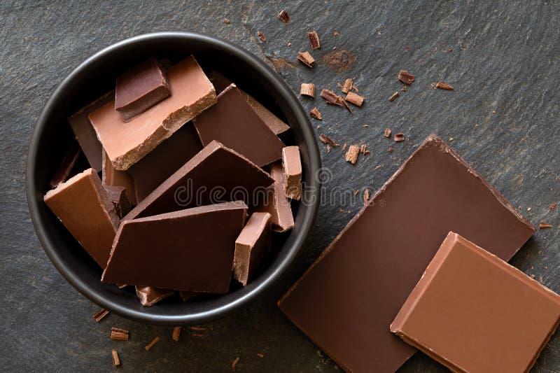 Stycken av mörker och mjölkar choklad i den svarta keramiska bunken som isoleras på grå färger, kritiserar från över Små bitar av arkivbilder