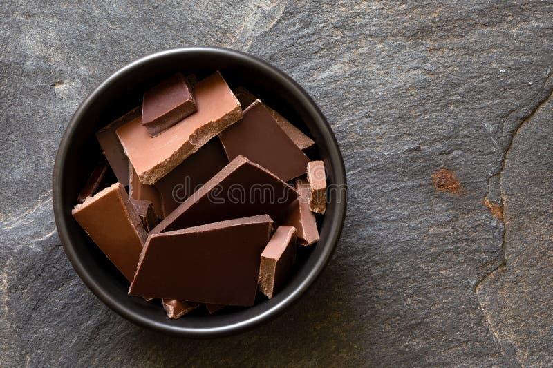 Stycken av mörker och mjölkar choklad i den svarta keramiska bunken som isoleras på grå färger, kritiserar från över Utrymme för  royaltyfria foton