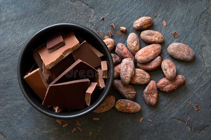 Stycken av mörker och mjölkar choklad i svart keramisk bunke bredvid kakaobönor som isoleras på grå färger, kritiserar från över royaltyfri fotografi