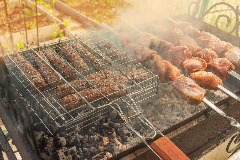 Stycken av marinerad köttkebab och chevapchichi som stekas på steknålar över en öppen brand Sommargrillfest Shashlik är en medbor royaltyfria bilder