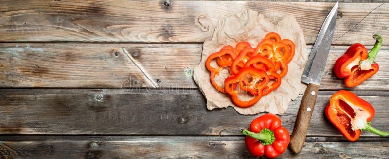Stycken av ny söt peppar på papper med en kniv royaltyfri bild