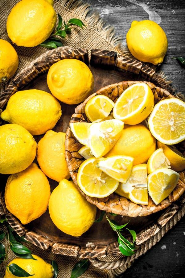 Stycken av nya citroner i en korg arkivbilder