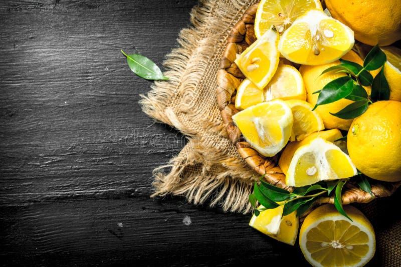 Stycken av nya citroner i en korg arkivfoto