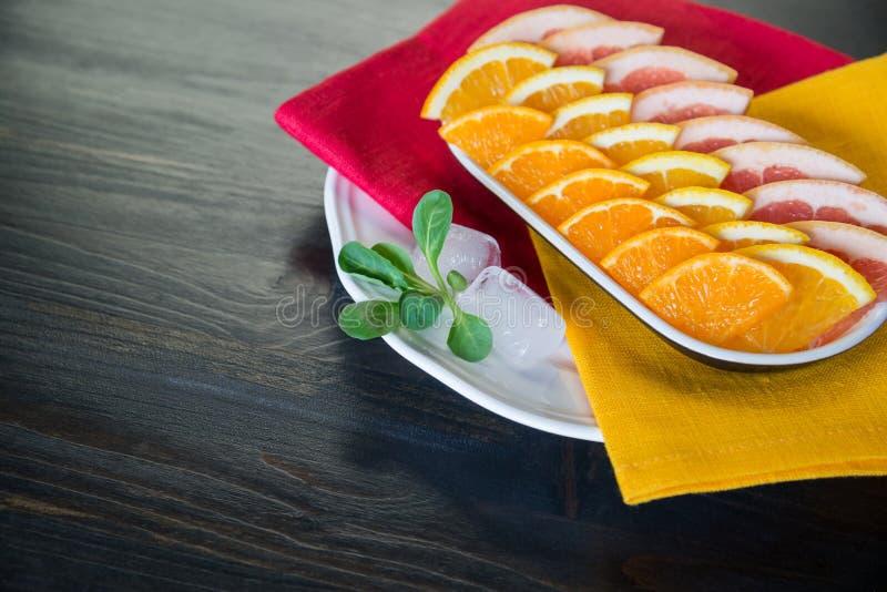 Stycken av nya citrusfrukter (grapefrukt, mandarin, apelsinen) arkivfoto