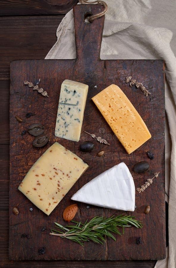 stycken av olika ostar p? ett brunt tr?br?de: brie roquefort, ost med muttrar arkivfoto