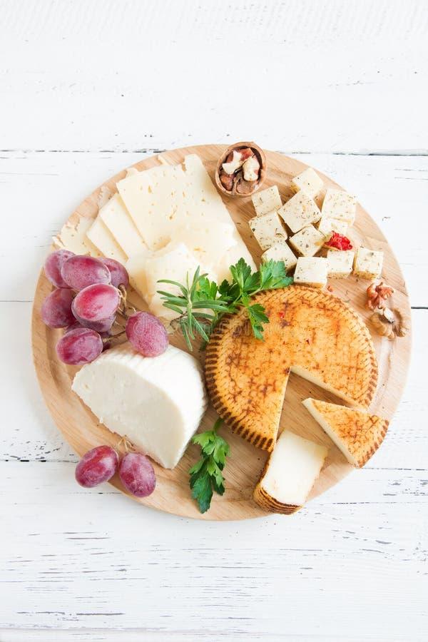 Stycken av ostar på woodenplatter arkivbilder