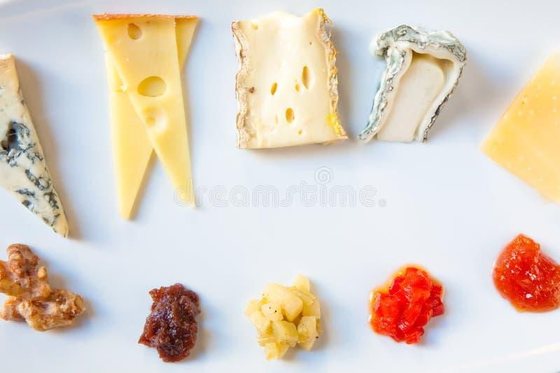 Stycken av ostar på woodenplatter arkivbild