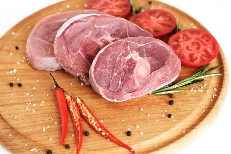 Stycken av rått kalkonkött, huggen av benbiff, portion grillfeststycken, på ett runt träbräde fotografering för bildbyråer