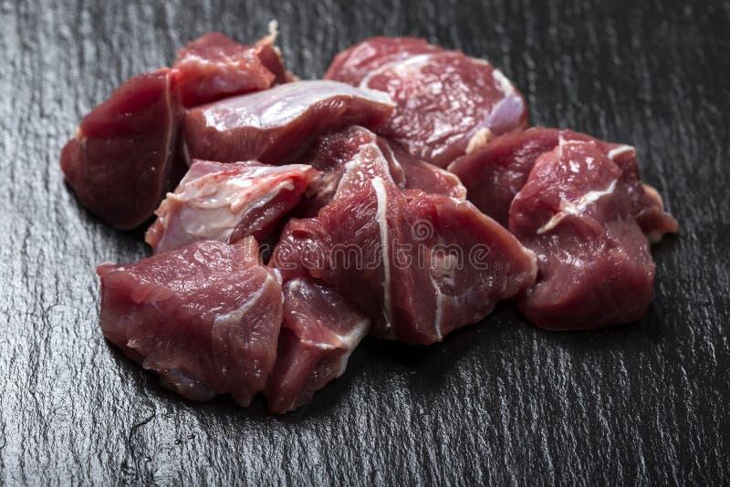 Stycken av rått nötköttkött på ett mörker kritiserar royaltyfria foton