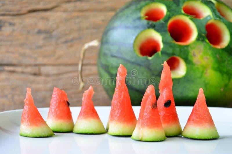 Stycken av röd frukt med vita och gröna skal av vattenmelonslutet upp royaltyfria foton