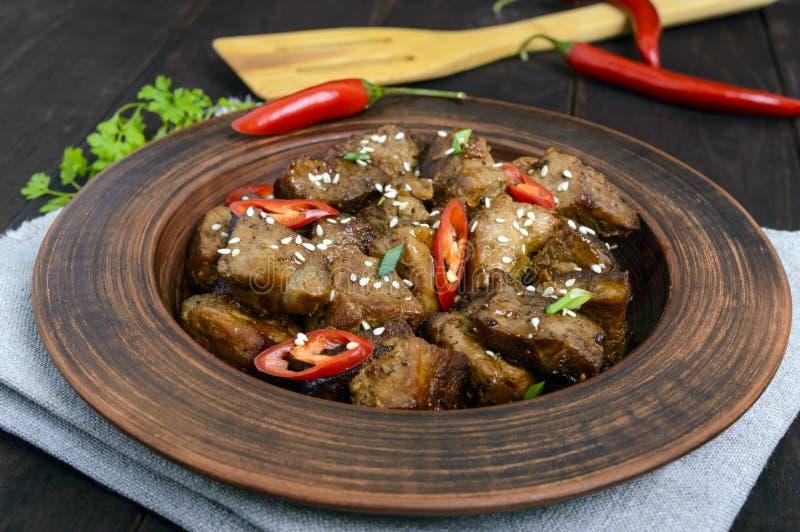 Stycken av stekt griskött med chili i en lerabunke royaltyfri fotografi