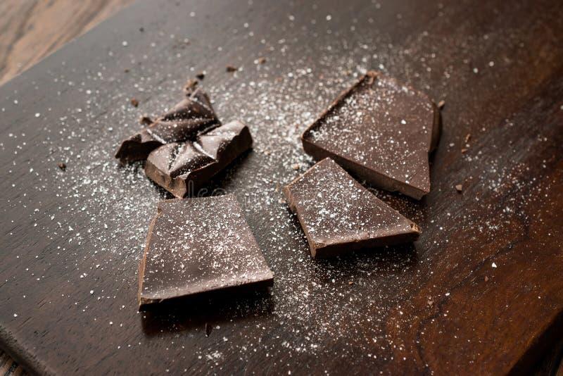 Stycken för bitter choklad med havet saltar på mörk träyttersida arkivbild