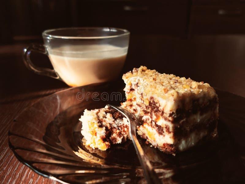 Stycket av chokladkakan på en platta och en kopp kaffe med mjölkar på en mörk trätabell i köket royaltyfri foto