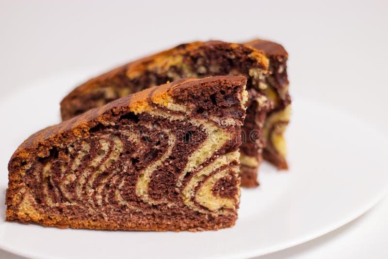 Stycket av den hemlagade choklad- och vaniljkakasebran bakar ihop marmorkakan Vit bakgrund Selektivt fokusera arkivfoto