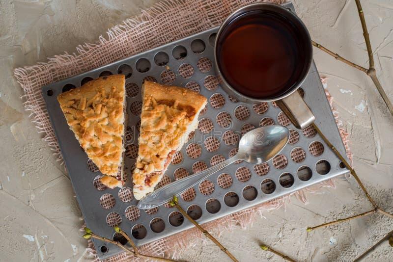 Stycket av fruktkakan med jordgubben, kiwin, persikan, äpplet, vaniljsåskräm och kopp te på bakgrundsjärnek förgrena sig med bäre arkivfoto