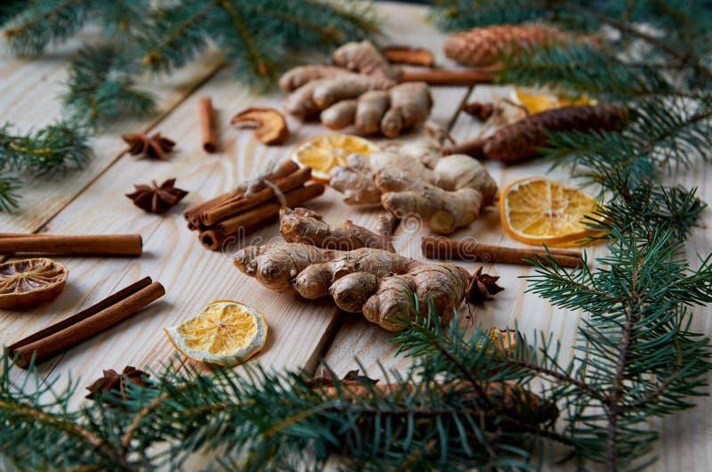 Stycket av ingefäran på träbakgrunden med traditionella kryddaingredienser för bageri funderade den vin torkade apelsinen, äpplet royaltyfri bild