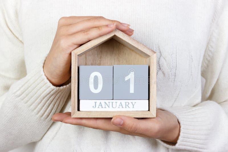 Styczeń 1 w kalendarzu dziewczyna trzyma drewnianego kalendarz nowy rok, ŚWIATOWY dzień pokój Uczta Mary obrazy stock