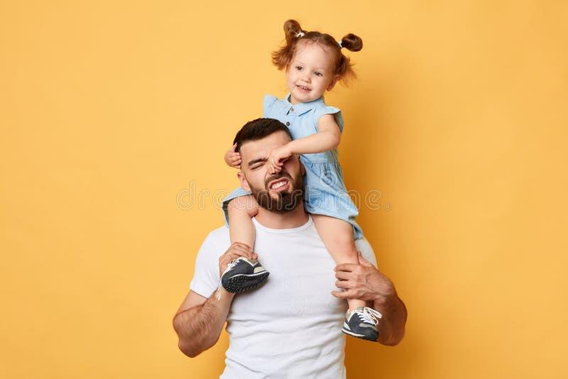 Stygg flicka som rymmer hennes pappas näsa, negativ skärm, ilsket uppförande royaltyfri foto