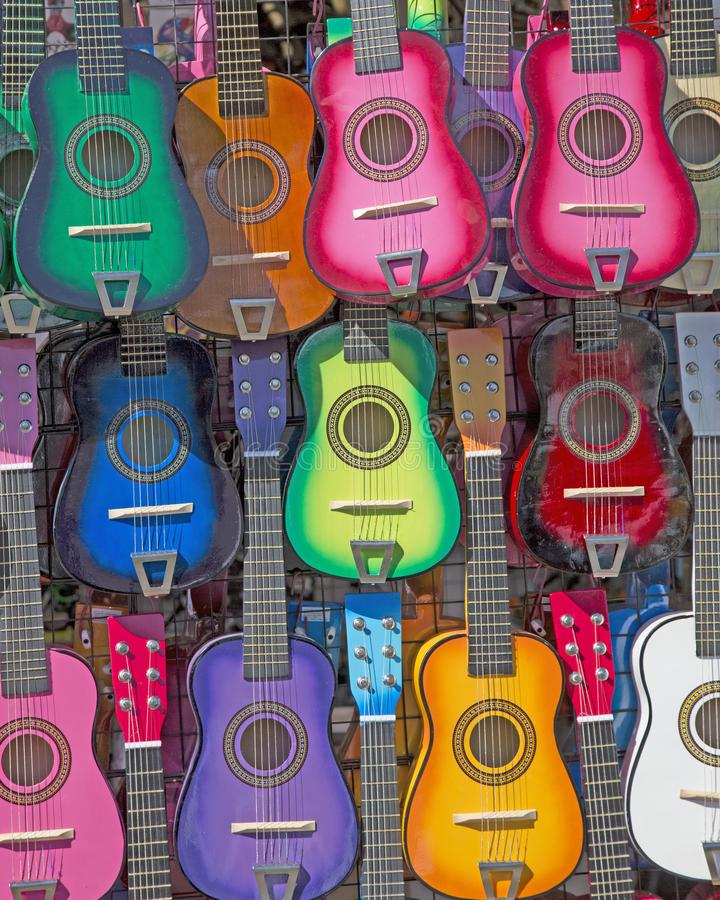 Styilized, Isolated Frontal View of Colorful Small Children`s Guitars Hanging Up - Horizontal Format stock image