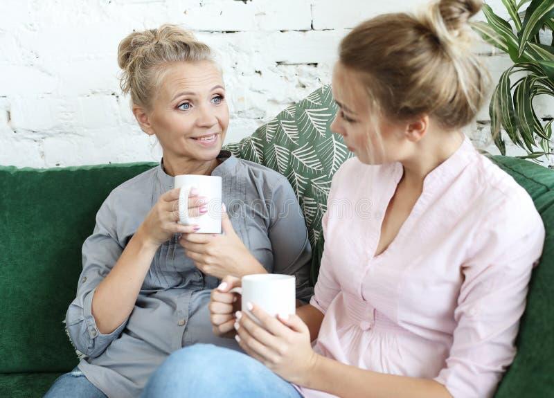 Styl życia i ludzie pojęć: Dwa pięknej kobiety matka i córki obsiadanie na kanapie w domu zdjęcia royalty free