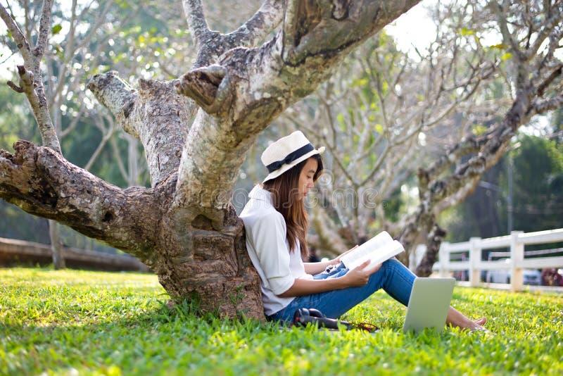 Styl życia dziewczyna cieszy się słuchającą muzykę i czytanie sztuka laptop na trawy polu natura park w ranku gree i książka fotografia royalty free