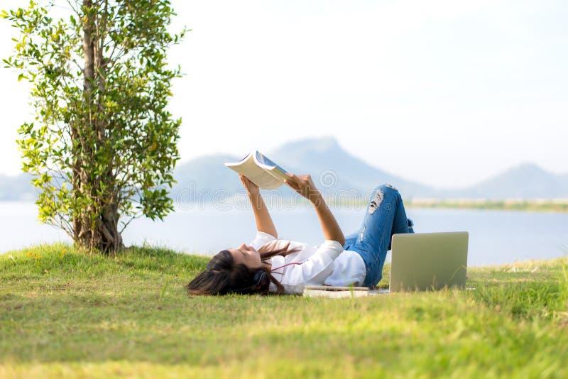 Styl życia dziewczyna cieszy się słuchającą muzykę i czytanie sztuka laptop na trawy polu natura park w ranku gree i książka zdjęcia royalty free