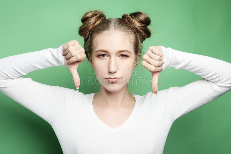 Styl życia, emocja i ludzie pojęć: Kciuka puszka znak, młoda kobieta z nieszczęśliwym negatywnym wyrażeniem fotografia royalty free