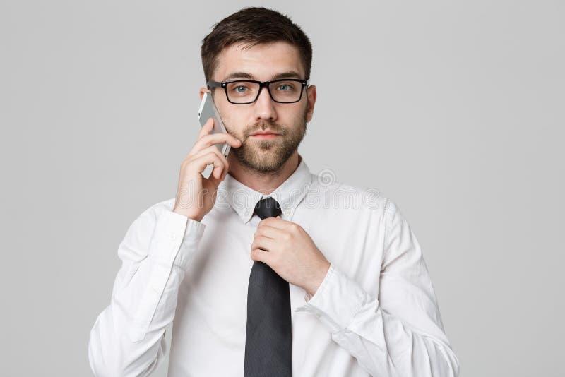 Styl życia i biznesu pojęcie - portret przystojnego biznesmena poważny opowiadać z telefonem komórkowym Odosobniony biały tło obraz royalty free
