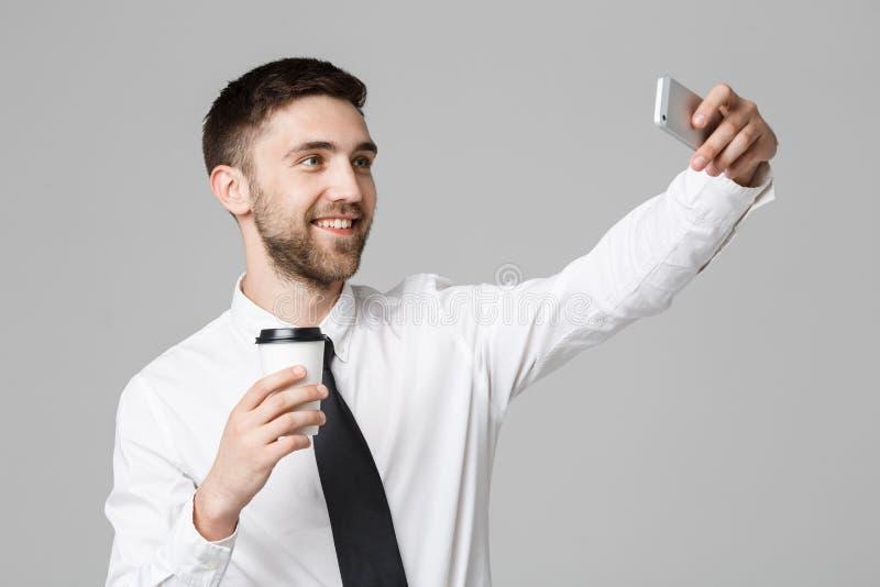 Styl życia i biznesu pojęcie - portret przystojny biznesmen cieszy się brać selfie z bierze oddaloną filiżankę kawy Odosobniony w obrazy royalty free