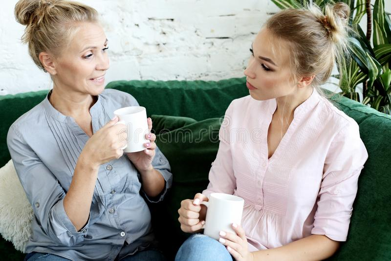 Styl życia i ludzie pojęć: Dwa pięknej kobiety matka i córki obsiadanie na kanapie w domu zdjęcie royalty free