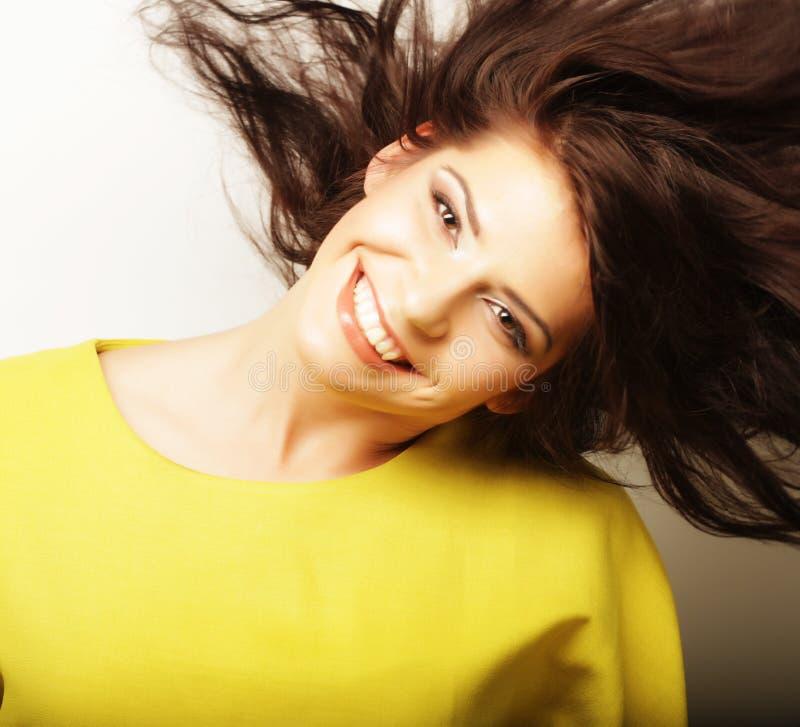 Styl życia i ludzie pojęć: Młoda śliczna uśmiechnięta kędzierzawa dziewczyna jest ubranym żółtą koszulkę nad białym tłem obraz stock