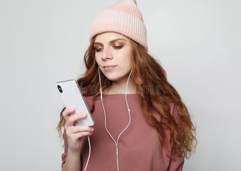 Styl życia i ludzie pojęć: młoda kobieta słucha muzyka w hełmofonach z smartphone obrazy royalty free