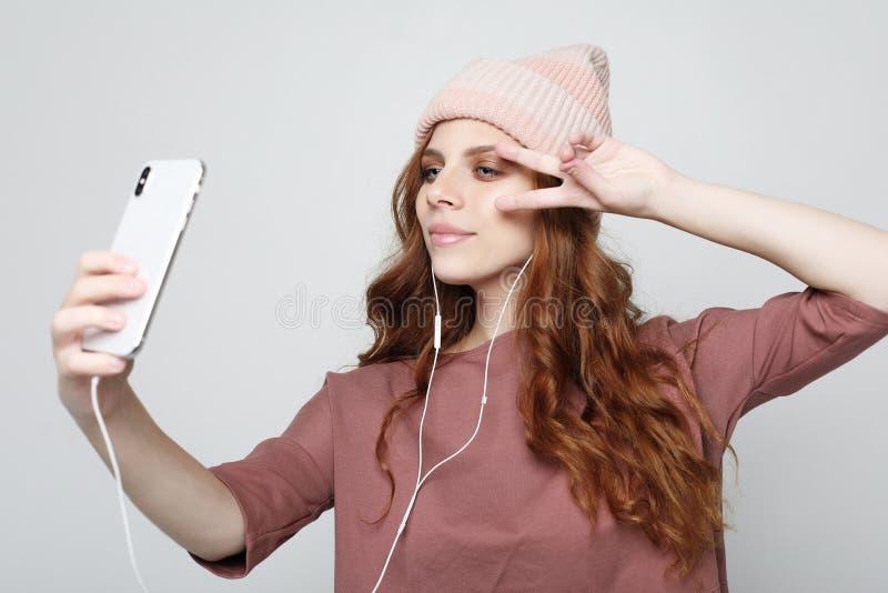 Styl życia i ludzie pojęć: młoda kobieta słucha muzyka w hełmofonach z smartphone zdjęcia stock