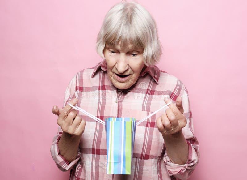 Styl życia i ludzie pojęć: Szczęśliwa starsza kobieta z torba na zakupy nad różowym tłem fotografia stock